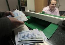 Мужчина пересчитывает купюры в обменном пункте в Минске 15 сетября 2011 года. Белорусский регулятор не исключил снижения ставки рефинансирования до 16 процентов в 2015 году благодаря замедлению инфляции и на фоне укрепления белорусской национальной валюты к упавшему российскому рублю. REUTERS/Vasily Fedosenko