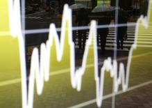 Экран с графиком динамики индекса Nikkei у брокерской конторы в Токио 11 ноября 2014 года. Азиатские фондовые рынки выросли в среду за счет благоприятных местных новостей. REUTERS/Yuya Shino
