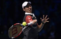 Kei Nishikori of Japan returns the ball to Roger Federer of Switzerland during their tennis match at the ATP World Tour finals at the O2 Arena in London November 11, 2014. REUTERS/Toby Melville