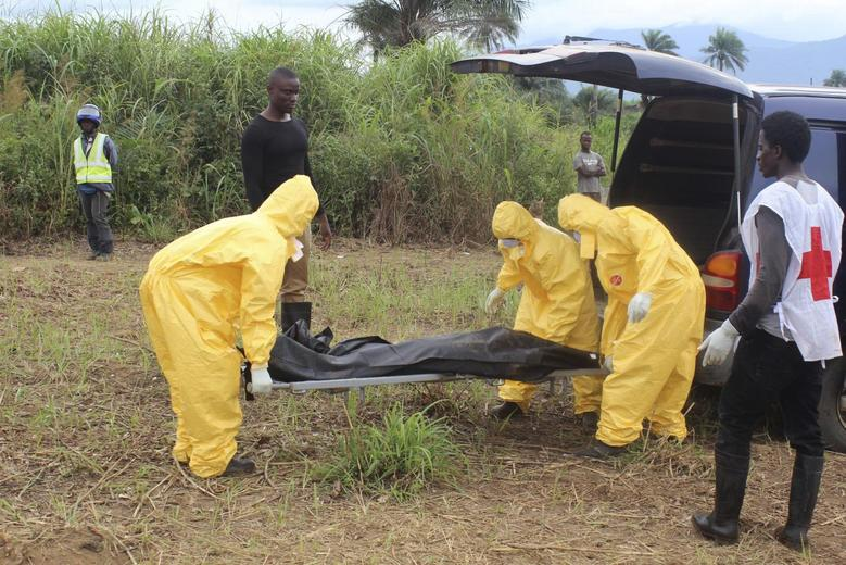 Health workers carry the body of an Ebola virus victim in the Waterloo district of Freetown, Sierra Leone, October 21, 2014.  REUTERS/Josephus Olu-Mamma