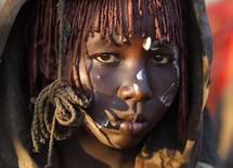 A Pokot girl, covered in animal skins, walks to a place where she will rest after being circumcised in a tribal ritual in a village about 80 kilometres from the town of Marigat in Baringo County, October 16, 2014. REUTERS/Siegfried Modola