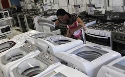 Mulher com criança no colo examina máquina de lavar em uma loja de São Paulo. 18/02/2013.  REUTERS/ Nacho Doce