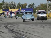 Uruguayan President Jose Mujica drives his Volkswagen Beetle (2nd R) during a Volkswagen Beetle race at the Pinar speedway on the outskirts of Montevideo May 13, 2012. REUTERS/Uruguayan Presidency/Handout