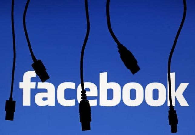Electronic cables are silhouetted next to the logo of Facebook in this September 23, 2014 illustration photo in Sarajevo.   REUTERS/Dado Ruvic