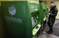 Люди у банкоматов Сбербанка в Санкт-Петербурге 5 ноября 2014 года. Крупнейший госбанк РФ Сбербанк видит признаки стабилизации на валютном рынке, допускает еще одно повышение ставок по рублевым депозитам до конца года и ожидает рецессию в 2015 году. REUTERS/Alexander Demianchuk
