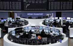 Traders are pictured at their desks in front of the German share price index DAX board at the Frankfurt stock exchange November 18, 2014.     REUTERS/Remote/Stringer