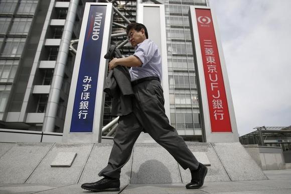 A pedestrian walks past signboards of Bank of Tokyo-Mitsubishi UFJ (R) and Mizuho Bank in Tokyo May 14, 2014. REUTERS/Yuya Shino