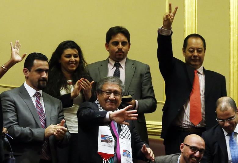 Palestinian delegate to Spain Musa Amer Odeh (C, with the scarf) celebrates after Spanish lawmakers approved a non-biding motion urging their government to recognize Palestine as a state, albeit only when the Palestinians and Israel negotiate a solution to their long-running conflict, at the Spanish Parliament in Madrid November 18, 2014. REUTERS/Susana Vera