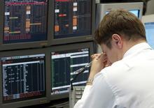 Трейдер Альфа-банка. Фотография сделана в Москве 5 июля 2004 года. Российские фондовые индексы в начале сессии среды вращаются вокруг сложившихся уровней, а слабее рынка выглядят акции Уралкалия, который накануне остановил рудник из-за угрозы безопасности. REUTERS/Sergei Karpukhin