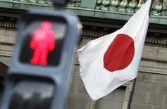 Японский флаг и светофор у здания ЦБ в Токио 19 ноября 2014 года. Банк Японии в среду не изменил монетарную политику и оптимистичный взгляд на экономику страны, несмотря на данные о начавшейся рецессии, предпочитая потратить больше времени, чтобы оценить влияние мер, принятых месяцем ранее. REUTERS/Yuya Shino