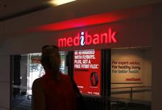 Женщина у офиса страховой компании Medibank Private в Сиднее 20 октября 2014 года. Австралия в среду повысила диапазон размещения для обещающего стать крупнейшим за два года IPO государственного страховщика Medibank Private Ltd из-за ажиотажного спроса. REUTERS/David Gray