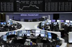 Traders are pictured at their desks in front of the German share price index DAX board at the Frankfurt stock exchange November 19, 2014.     REUTERS/Remote/Stringer