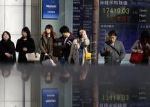 Personas frente a una pantalla electrónica que muestra el índice Nikkei en Tokio, 19 noviembre, 2014. La mayoría de las bolsas de Asia caían el jueves luego de que unos débiles datos de producción fabril china redujeron la confianza de los inversores, y el yen cedió a mínimos en varios años contra el dólar y el euro. REUTERS/Yuya Shino