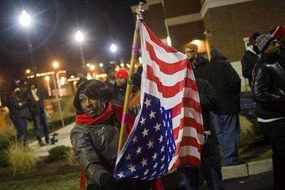 A protester, who was among dozens demanding the criminal indictment of a white police officer who shot dead an unarmed black teenager in August, holds a U.S. flag upside down outside the Ferguson Police Station in Missouri, November 20, 2014. Credit: Reuters/Adrees Latif