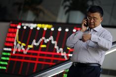 """Un hombre habla por su celular en la bolsa de Shanghái en el distrito financiero de Pudong. Imagen de archivo, 17 noviembre, 2014.  Las bolsas de Asia subían el viernes luego de que unos datos mostraron un fortalecimiento de la economía de Estados Unidos, y el yen rebotaba desde mínimos en varios años después que el ministro de Finanzas de Japón advirtió que su debilitamiento reciente ha sido """"demasiado rápido"""". REUTERS/Carlos Barria"""