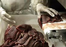 Foto de arquivo de um açougueiro cortando pedaços de carne em abatedouro em São Paulo. 09/09/2005 REUTERS/Paulo Whitaker