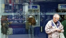 A man stands outside a building as people use Intesa Sanpaolo automated teller machines (ATMs) in Milan October 1, 2013.  REUTERS/Stefano Rellandini