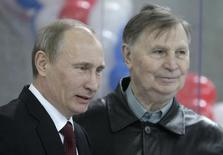 "Russia's Prime Minister Vladimir Putin (L) and ice hockey legendary coach Viktor Tikhonov attend the ""Golden Puck"" youth tournament finals at Luzhniki arena in Moscow April 16, 2011. REUTERS/Mikhail Metzel/Pool"