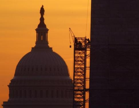 A bucket is lifted by scaffolding workers at the Washington Monument (R) at sunrise in Washington March 15, 2013. The U.S. Capitol is seen at left. REUTERS-Gary Cameron