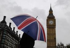 Uma mulher com guarda-chuva nas cores da bandeira do Reino Unido à frente do Big Ben. 04/10/2014 REUTERS/Luke MacGregor