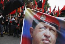 Membros do Movimento Revolucionário Tupamaro seguram cartaz com foto de Hugo Chávez em protesto em apoio ao presidente da Venezuela, Nicolás Maduro, em Caracas. 09/05/2014 REUTERS/Carlos Garcia Rawlins