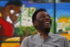 Brazilian soccer legend Pele laughs during the inauguration of a refurbished soccer field at the Mineira slum in Rio de Janeiro September 10, 2014.  REUTERS/Ricardo Moraes/Files