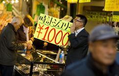 Sur le marché d'Ameyoko à Tokyo. L'inflation au Japon a ralenti en octobre pour le troisième mois consécutif, en raison de la baisse des prix du pétrole, soulignant la morosité de la conjoncture à quinze jours des élections convoquées par le Premier ministre, Shinzo Abe, pour valider sa politique économique. /Photo prise le 27 novembre 2014/REUTERS/Thomas Peter