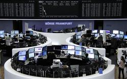 Traders are pictured at their desks in front of the German share price index DAX board at the Frankfurt stock exchange November 28, 2014.     REUTERS/Remote/Stringer