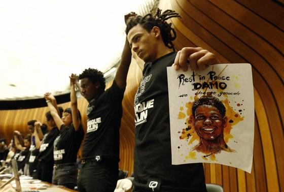 Activists hold hands during a silent protest at a hearing of the United States at the Committee against Torture at the United Nations in Geneva November 13, 2014.  REUTERS-Denis Balibouse