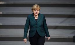German Chancellor Angela Merkel walks down the stairs in the lower house of parliament Bundestag in Berlin, November 26, 2014. REUTERS/Stefanie Loos