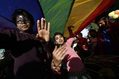 Participants dance under a giant rainbow flag during Delhi Queer Pride Parade, an event promoting gay, lesbian, bisexual and transgender rights, in New Delhi November 30, 2014. REUTERS/Adnan Abidi