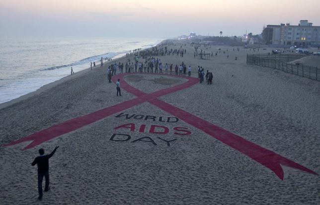 Beach goers look at a red ribbon sand sculpture created by Indian sand artist Sudarshan Patnaik to create awareness about AIDS on the eve of World AIDS Day on a beach in Puri in the eastern Indian state of Odisha November 30, 2014. REUTERS/Stringer