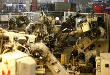 A worker watches robots at Futaba Industrial in Foston, central England January 21, 2014. REUTERS/Darren Staples