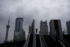 Una mujer sostiene un paraguas en una escalera en el distrito financiero de Pudong, Shanghái. Imagen de archivo, 25 noviembre, 2014. El crecimiento en el sector manufacturero de China se desaceleró en noviembre, lo que sugiere que la segunda economía más grande del mundo sigue perdiendo impulso y agrega presión sobre las autoridades para que incrementen las medidas de estímulo después de recortar las tasas de interés el mes pasado. REUTERS/Aly Song