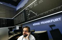 A trader is pictured at his desk in front of the German share price index DAX board at the Frankfurt stock exchange December 2, 2014.       REUTERS/Ralph Orlowski