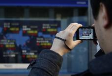 Pedestre tira foto de painel eletrônico com cotações de ações do lado de fora de corretora, em Tóquio. 24/12/2013 REUTERS/Yuya Shino