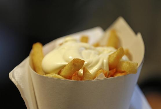 A large cone of fries with mayonnaise sauce is pictured at the Maison Antoine frites stand in Brussels December 4, 2014.  REUTERS/Yves Herman