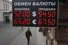 Мужчина проходит мимо вывески пункта обмена валюты в Москве 3 декабря 2014 года. Рубль дешевеет при открытии торгов понедельника в русле мировых тенденций снижения сырьевых и высокодоходных валют на фоне слабой внешнеторговой статистики Китая и после сильных данных о росте занятости в США, поддержавших курс американского доллара. REUTERS/Maxim Zmeyev