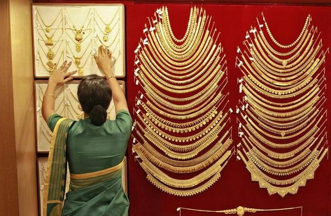 A saleswoman arranges a gold necklace inside a jewellery showroom in Kochi April 16, 2013. REUTERS/Sivaram V/Files