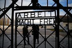 """Visitantes passam por um portão com a inscrição """"Arbeit macht frei""""(O trabalho liberta) no antigo campo de concentração de Dachau, na Alemanha. 25/01/2014. REUTERS/Michael Dalder"""