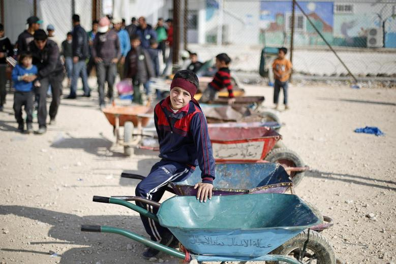 Syrian children wait to carry customers' goods using wheelbarrows, in front of the Tazweed Center at the Al-Zaatari refugee camp in the Jordanian city of Mafraq, near the border with Syria, December 7, 2014.  REUTERS/Muhammad Hamed