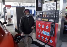 Un empleado carga combustible en una gasolinera en Turnersville, EEUU, dic 4 2014. El Gobierno de Estados Unidos recortó el martes su previsión sobre el aumento de la producción doméstica de petróleo en el 2015 en cerca de 100.000 barriles por día y redujo su pronóstico sobre el crecimiento de la demanda mundial de crudo el año próximo en 240.000 bpd.  REUTERS/Tom Mihalek