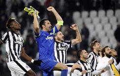 Goleiro Gianluigi Buffon, da Juventus, comemora classificação da equipe na Liga dos Campeões com companheiros de time após empate com o Atlético de Madri em Turim. 09/12/2014 REUTERS/Giorgio Perottino