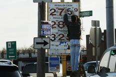 A man changes the price for a gallon of gasoline at a gas station in Medford, Massachusetts December 4, 2014. REUTERS/Brian Snyder