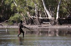 Australian Aboriginal hunter Roy Gaykamangu of the Yolngu people walks across a billabong while hunting a crocodile near the 'out station' of Yathalamarra, located on the outksirts of the community of Ramingining in East Arnhem Land November 22, 2014.       REUTERS/David Gray