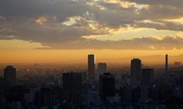 Rascacielos son vistos durante el atardecer en Tokio. Imagen de archivo, 10 diciembre, 2013. Fitch Ratings espera rebajar la calificación crediticia de Japón en algún momento a comienzos del año próximo, ya que es poco probable que el Gobierno compile un presupuesto para el próximo año fiscal que compense un retraso en el alza del impuesto sobre las ventas, dijo el jueves un funcionario de alto rango de la agencia. REUTERS/Toru Hanai