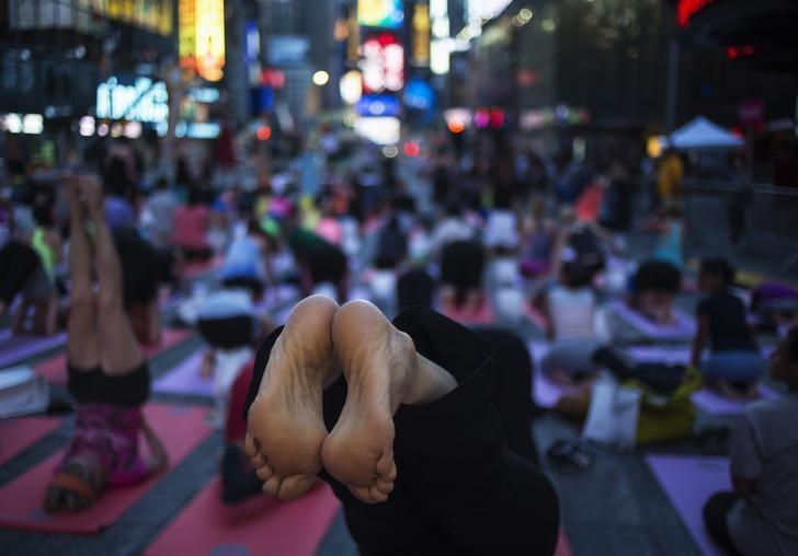 People practice yoga in Times Square as part of a Summer Solstice celebration in New York June 21, 2014. REUTERS/Eric Thayer/Files