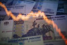 Рублевые купюры на фоне графика изменения курса рубля к доллару в Варшаве 7 ноября 2014 года. Рубль дешевеет утром пятницы, обновив абсолютные минимумы на фоне приближения нефтяных котировок к самым низким значениям за последние 5,5 лет. REUTERS/Kacper Pempel
