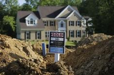 A completed house (rear) is seen behind the earthworks of a home currently under construction at the Mid-Atlantic Builder's 'The Villages of Savannah' development site in Brandywine, Maryland May 31, 2013.   REUTERS/Gary Cameron