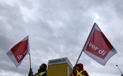 Membros do sindicato Verdi com bandeiras do lado de fora de um armazém da Amazon. 15/12/2014 REUTERS/Michaela Rehle